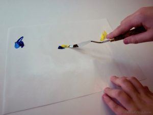 mixing blue and yellow paint with palette knife
